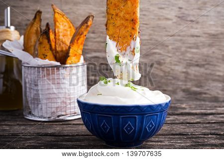 Sweet potato fries in paper wrap executed in metal serving basket with fresh cream dip souce on old wooden table.