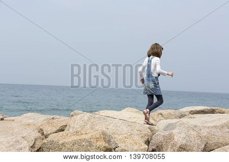 little girl jumping on the rock along the sea