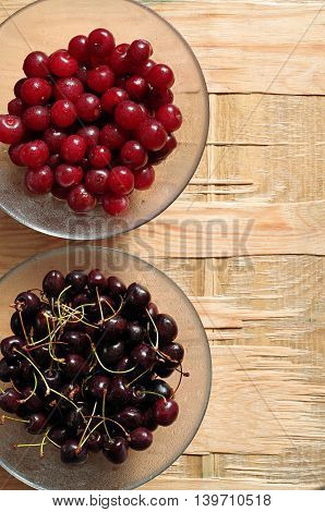 Cherry with water drops in glass bowl on old wooden background top view
