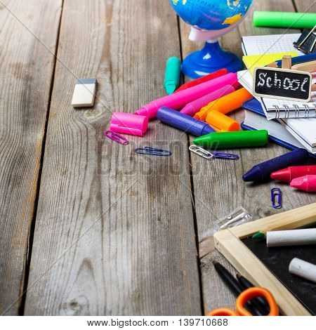 Assortment of office and school supplies, alarm clock and chalkboard on a rustic wooden table. Selective focus, copy space background