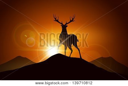 Silhouettte of deer on a mountain peak against sunset landscape.