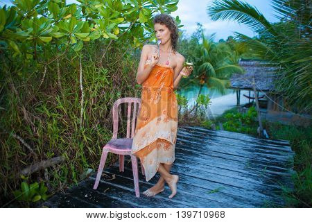 Photo young girl enjoying tropical fruits in jungle house. Smiling woman spending chill time outdoor summer. Horizontal picture, Bali island