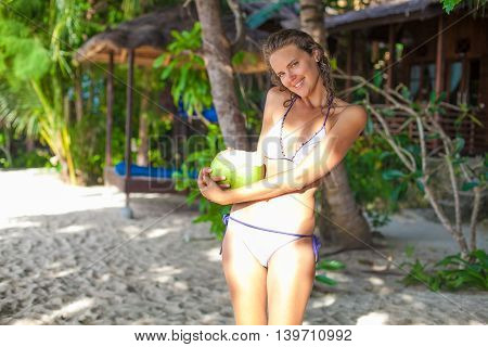 Photo young girl relaxing on beach with coconut. Smiling woman spending chill time outdoor summer Bali island. Horizontal picture