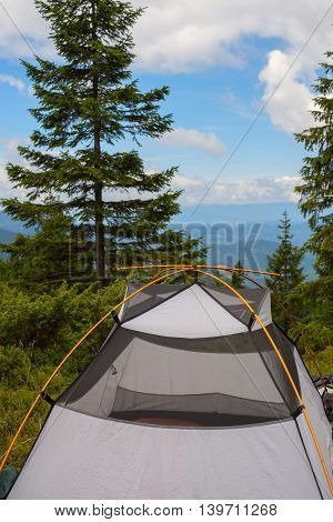Trekking in Carpathian Mountains. Tent camp in the coniferous forest on a background of mountains covered with clouds