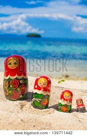 Photo Rows Puzzle Russian Dolls Matrioshka Souvenir Untouched Tropical Beach in Bali Island. Vertical Picture. Blurred Background. Closeup