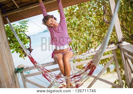 Photo young sexy girl relaxing on beach in Bungalow. Smiling woman spending chill time outdoor summer. Caribbean Ocean Vacations. Horizontal, blurred background