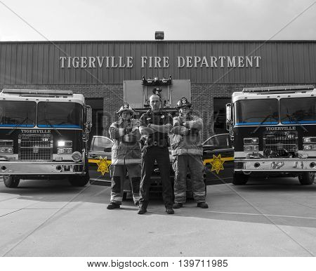 Firefighters standing behind police officer selective color
