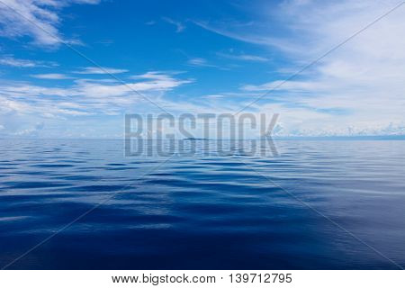 Photo of Blue Sea and Tropical Sky Clouds. Seascape. Sun over Water, Sunset. Horizontal picture