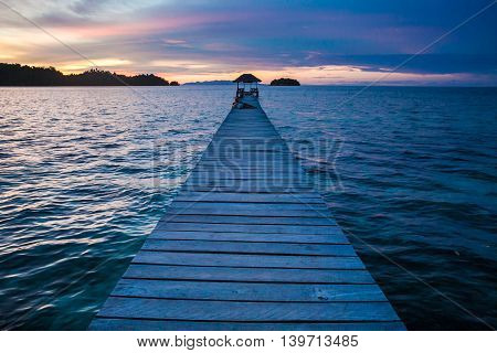 Photo Bungalow Pier in Indonesia Village Tropical Beach in Bali Island. Summer Season Caribbean ocean. Romantic View Point Sunset. Horizontal Picture