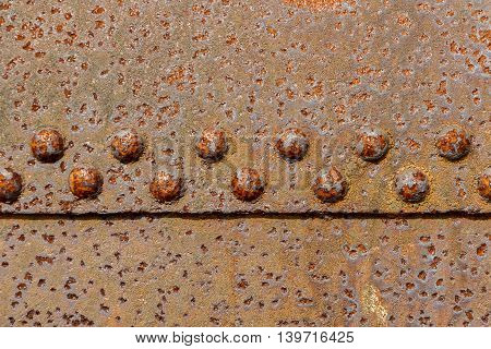 Close up shot of rusting iron held together with bolts
