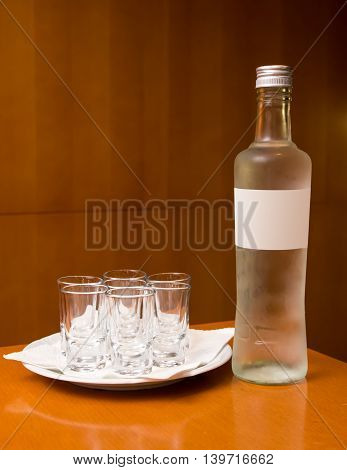 Bottle with alcohol and short drinks on wooden background