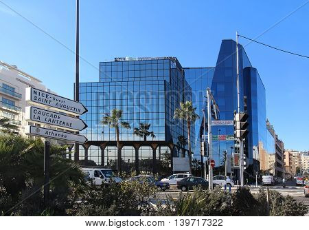NICE FRANCE - FEBRUARY 03; Road signs in city center signpost close to promenade in Nice France - February 03 2016: Modern architecture buildings close to the road with direction traffic signs.