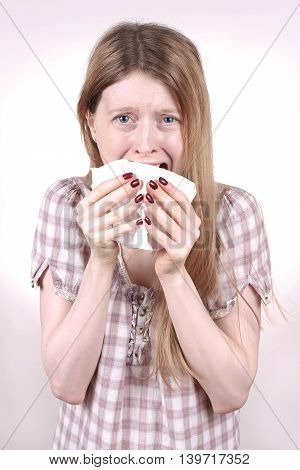 Young woman crying and holding paper tissue