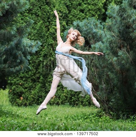Beautiful girl dressed in a tunic jumping in a summer park