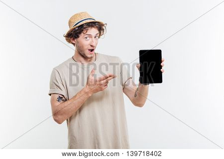 Portrait of a happy excited man pointing finger at tablet with blank screen isolated on a white background