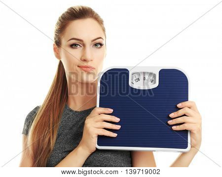 Beautiful young woman holding floor scales on white background