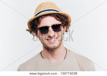 Closeup of cheerful young man in hat and sunglasses smiling over white background