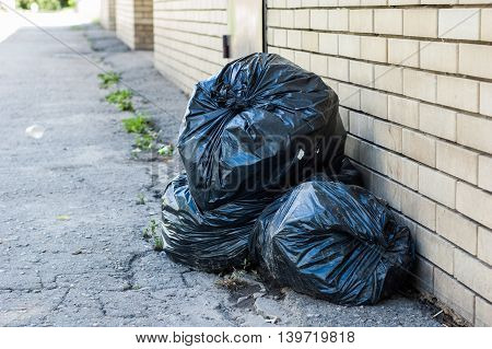 Several black bag of garbage lying on the streets.