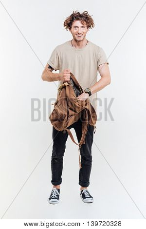 Young smiling man standing and getting something out of his backpack isolated on white background
