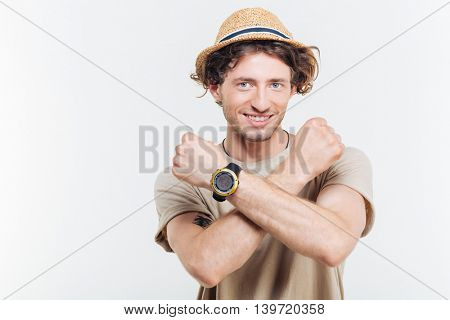 Portrait of a young stylish man showing stop gesture with arms crossed isolated on a white background