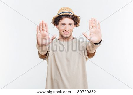 Smiling young man in a hat showing stop gesture with two palms over white background