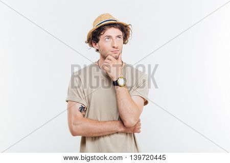 Thoughtful handsome young man standing and thinking over white background
