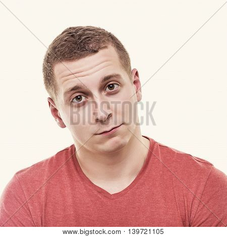 Man is looking indifferently on a white background. Toned photo.