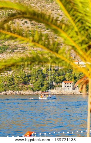 Luxury yacht sails on the Adriatic Sea coastline. Traveling near the island. The boat is sailing into the port. Dubrovnik, Croatia