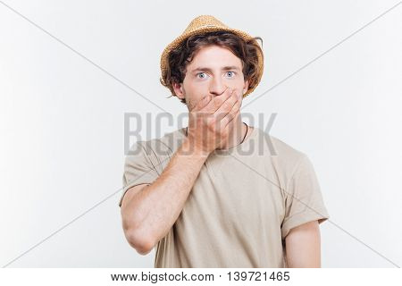 Handsome young man in hat coveres his mouth by hand over white background