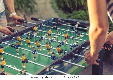 Cropped image of young people playing foosball while resting outdoors