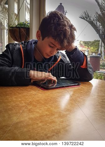Boy at table in low light in front of window resting on his elbow concentrating with hand poised over his mobile device