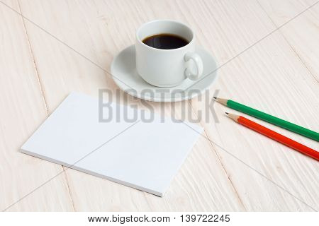 Cup of coffee a notebook and pencils on wooden table