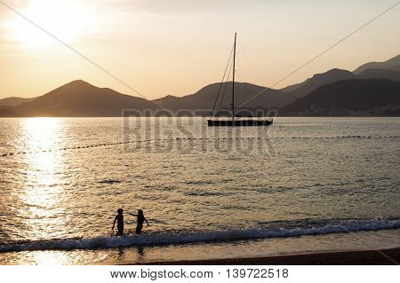 Yacht in the Adriatic sea at sunset. Beautiful gold sunset with a sailboat. Children are playing.