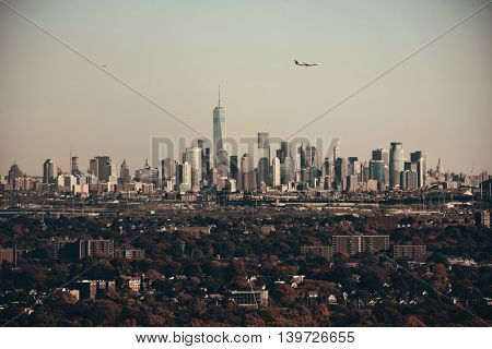 New York City skyline with airplane viewed from park with Autumn foliage