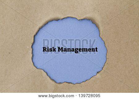 Risk Management concept written under torn paper