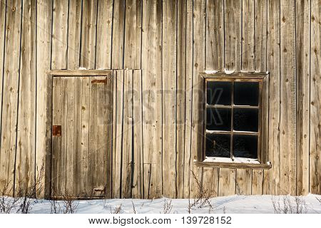 Door and window on wall of an old wooden barn at winter in Russia.