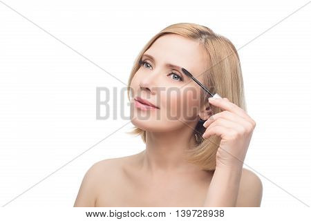 Beautiful middle aged woman with smooth skin and short blond hair applying fix gel to eyebrows. Beauty shot. Isolated over white background. Copy space.