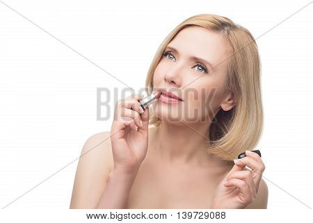 Beautiful middle aged woman with smooth skin and short blond hair applying lipstick. Beauty shot. Isolated over white background. Copy space.