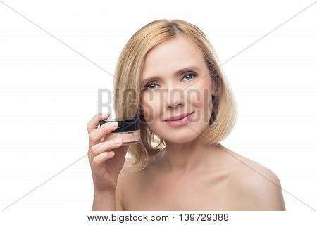 Beautiful middle aged woman with smooth skin and short blond hair with loose powder. Beauty shot. Isolated over white background. Copy space.