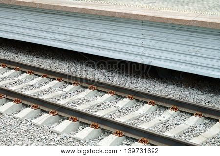 The railroad tracks close-up and platform to passengers.