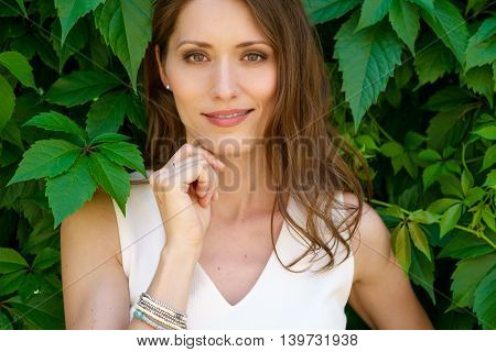 Portrait of smiling girl with long dark hair looking at camera. Fresh bright image