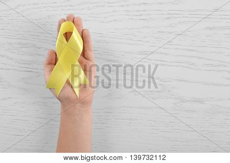 Woman hand with yellow ribbon on wooden background. Children cancer concept