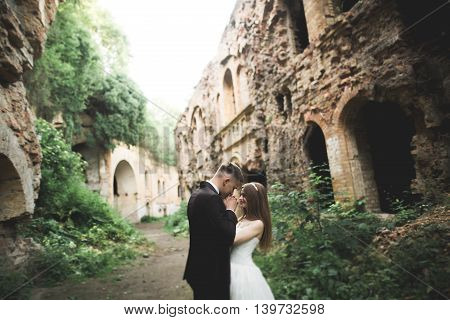 Just married poses in the light of sunset with an old fortress on the background.