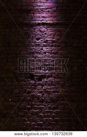 Shot of a brick wall texture illuminated with a purple light
