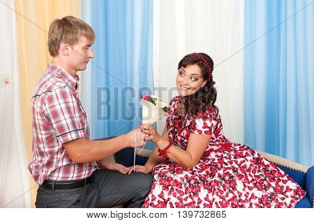 Beautiful couple man and woman meeting on the couch, he gives her flowers