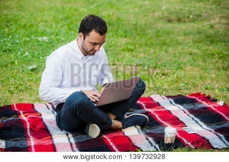 Thoughtful businessman in the field. With laptop.