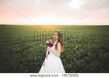 Closeup portrait of beautiful bride with wedding bouquet isolated at green natural summer field background.