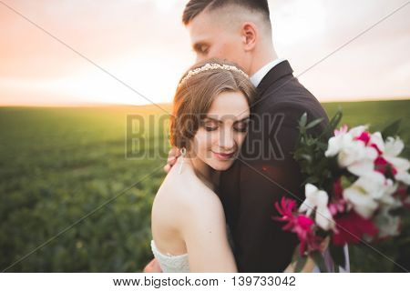 groom is holding and kissing his bride on the background sunset.