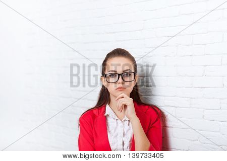 Businesswoman serious wear red jacket glasses hold chin ponder business woman over office wall