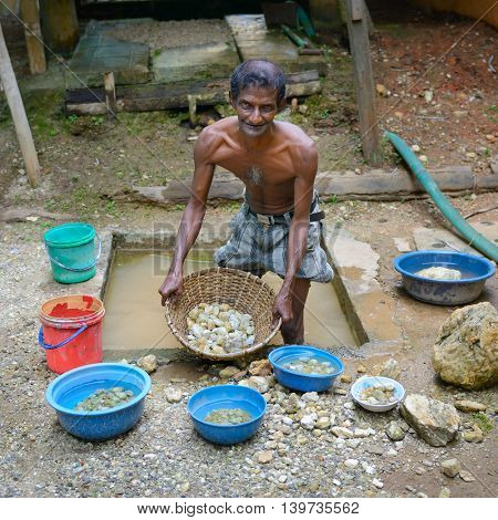 Sri Lanka - November 29, 2013: Unskilled worker at the mine for the extraction of precious stones. Editorial.
